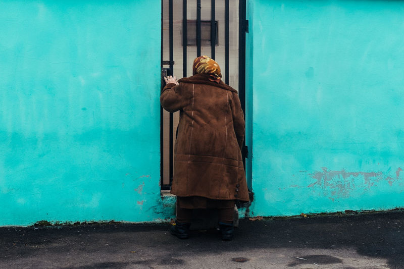 Woman wearing jacket standing at doorway by turquoise wall