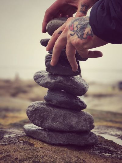 Cropped image of hands with tattoo stacking stones at beach