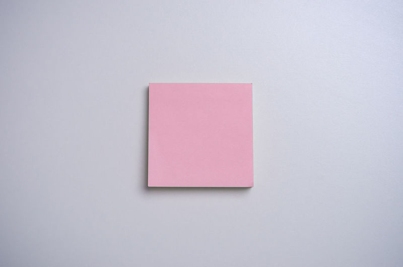 Pink sticky note on white desk. Note Sticky Pink Post Blank Paper White Background Notes Business Message Reminder Board Memo Empty Sheet Office Adhesive Space Clip Color Sticker Label Information Desk Blue Table Red List Do Slip Paperclip Modern Concept