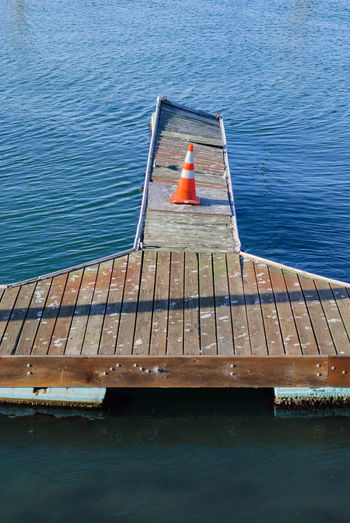Landing stage Attention Boat Day Orange Pier Plank Pylon Sea Water Wood