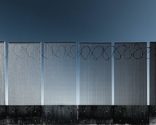 Metal fence against clear blue sky