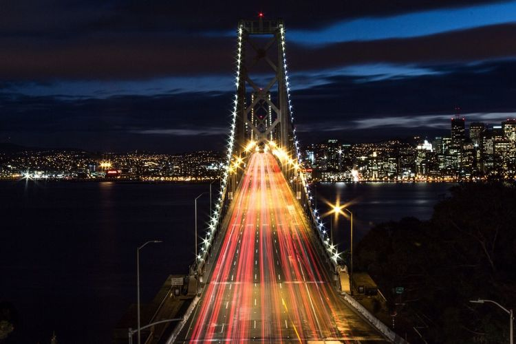 High angle view of light trails illuminated oakland bay bridge and cityscape at night