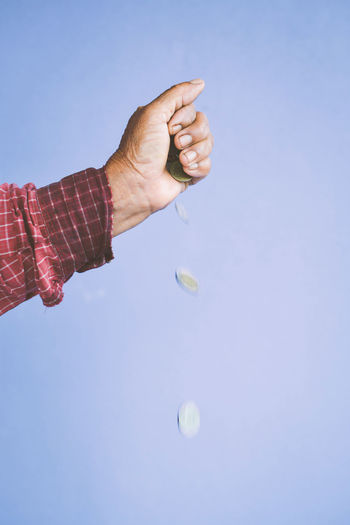 Cropped image of hand dropping coins against purple background