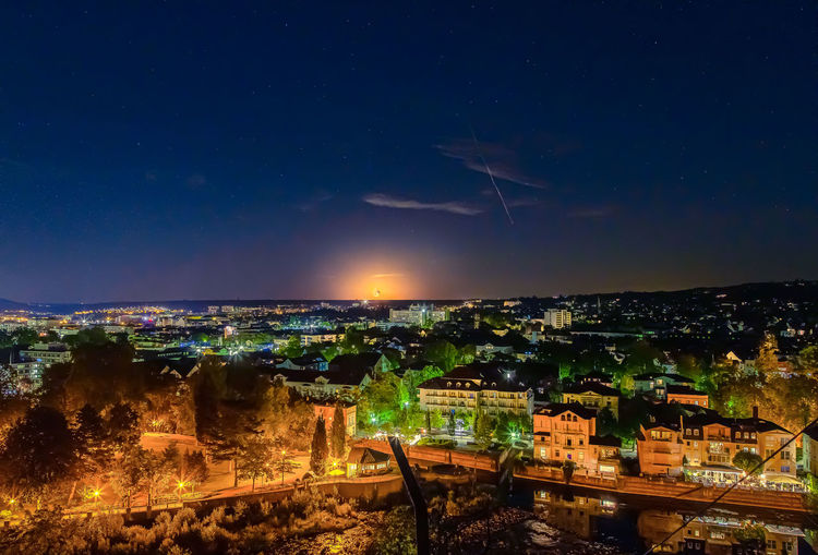 High angle shot of illuminated cityscape against sky at night