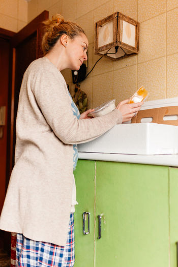 Side view of woman holding food from box at home