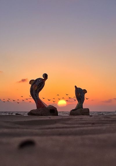 Close-up of statue on beach against sky during sunset