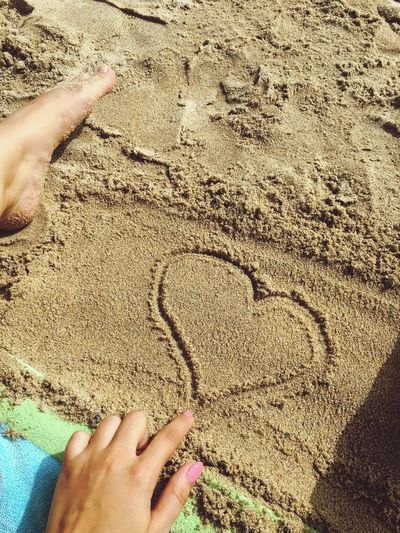 Close-up of woman making heart shape on sand