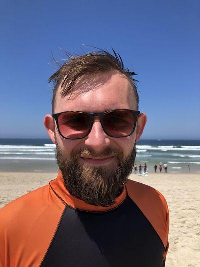 Portrait of man wearing sunglasses on beach against sky