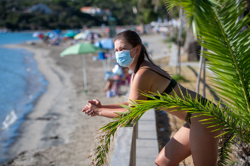 Side view of woman wearing mask standing by railing at beach