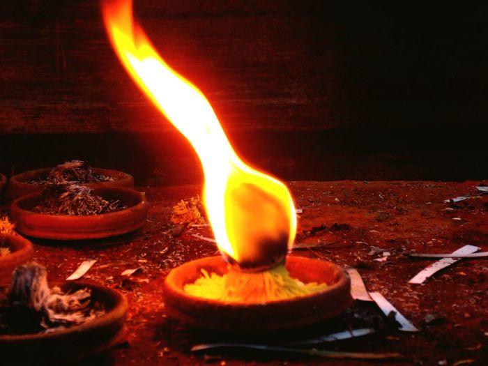 Close-up of burning candle on wood