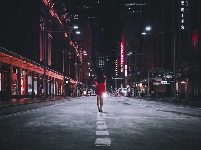 WOMAN ON ROAD IN CITY AT NIGHT