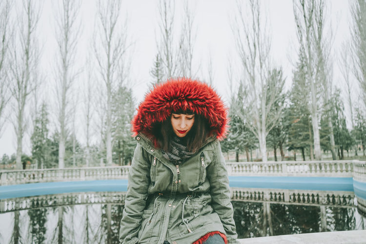 Woman in warm clothing sitting at railing against lake