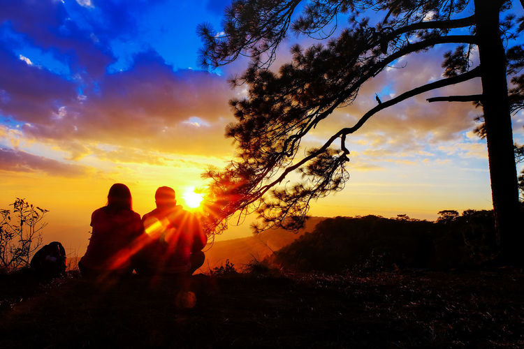 Silhouette people sitting on land against sky during sunset