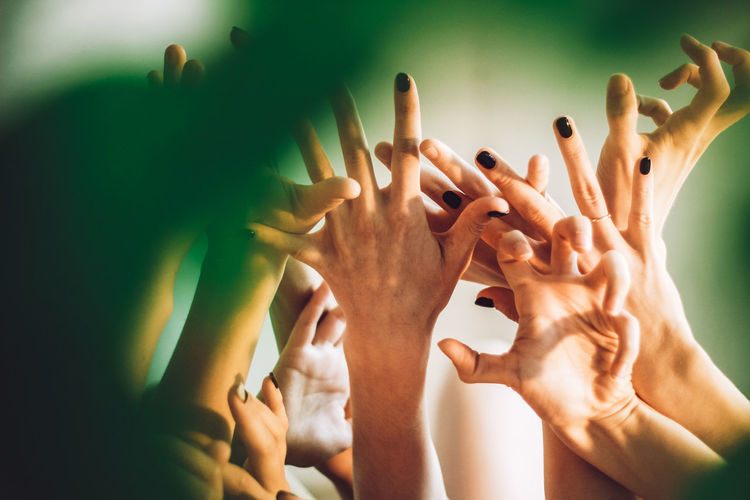 Cropped hands of female friends with arms raised against wall
