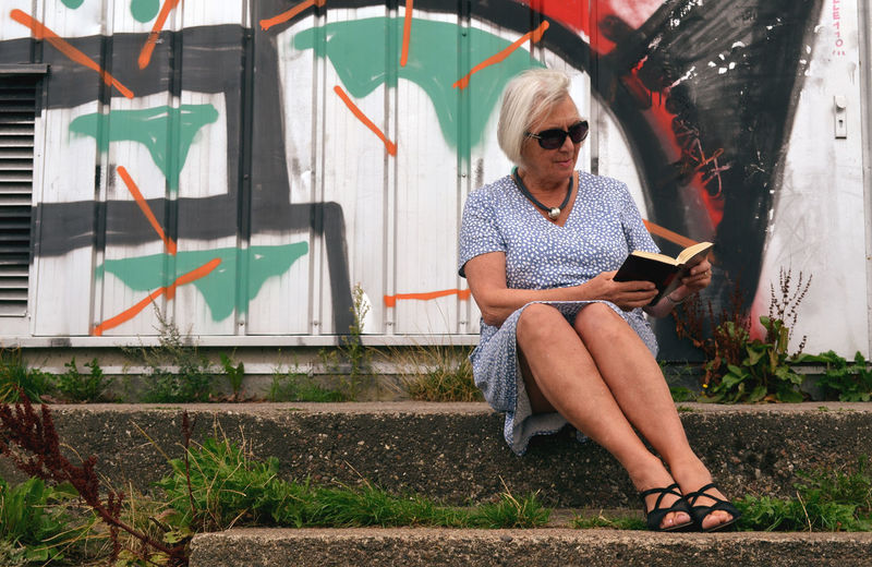 Urban Reading Contrast Over 65 Lady Odd Place #urbanana: The Urban Playground #urbanana: The Urban Playground One Person Creativity Graffiti Sitting Front View Adult Outdoors Lifestyles