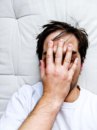 Man covering face while lying on bed at home