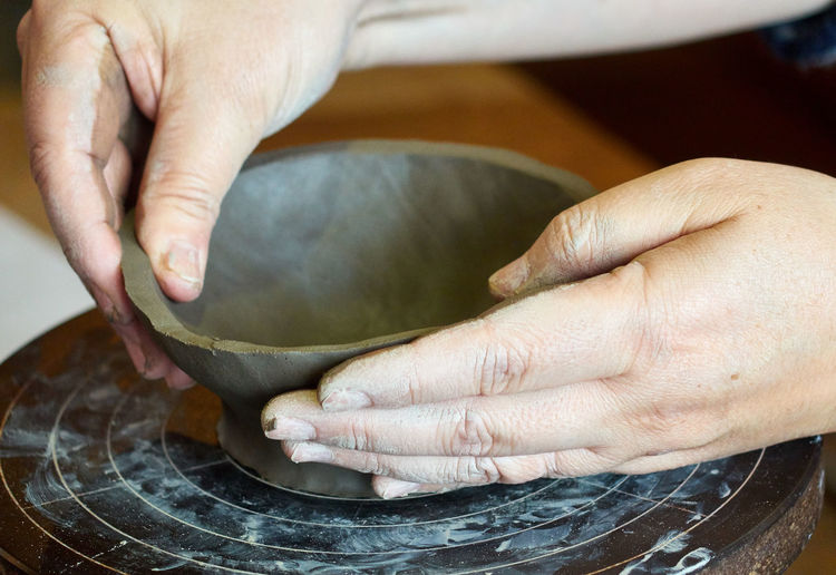 Close-Up Of Person Holding Clay Bowl