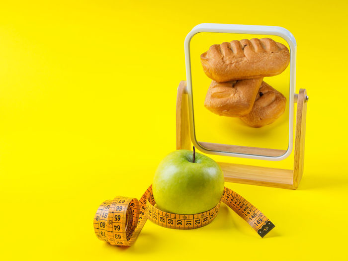 Close-up of apple on table against yellow background