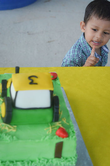Toddler admires his birthday cake Asian  Birthday Party Birthday Cake Celebration Dessert Indian Venue Birthday Boy British Indian Childhood Outdoor Venue Outdoors Party Theme Party Toddler  Tractor Theme