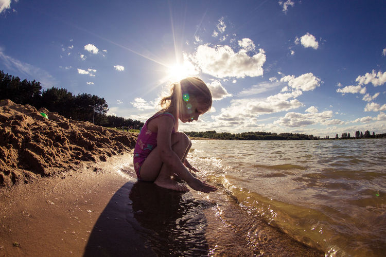 Girl Crouching At Sea Shore Against Sky