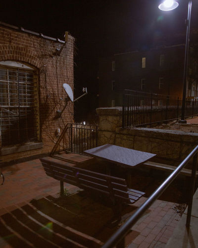 Empty bench by illuminated building at night