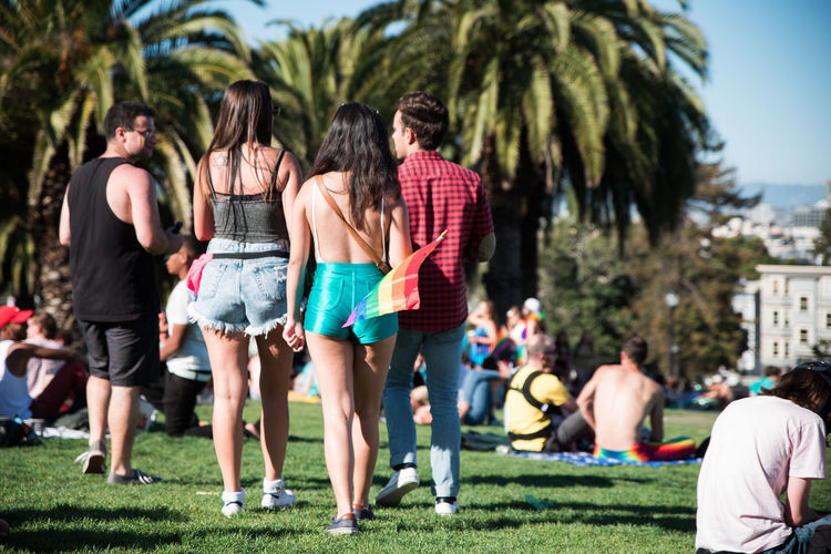 Marching through grass field on the pride weekend Casual Clothing Diversity Dolores Park Friendship Green Leisure Activity Lifestyles Medium Group Of People Outdoors Palm Trees Park Pride Pride 2016 Pride San Francisco Pride Weekend Rear View San Fransisco Side By Side Sunny Togetherness