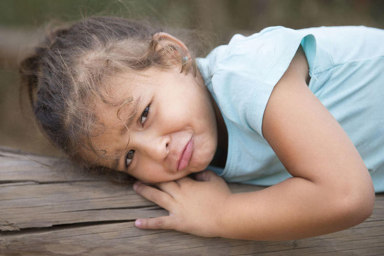 Portrait of cute girl lying on wood