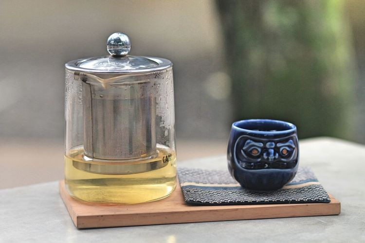 Close-Up Of Tea Infuser By Cup On Table