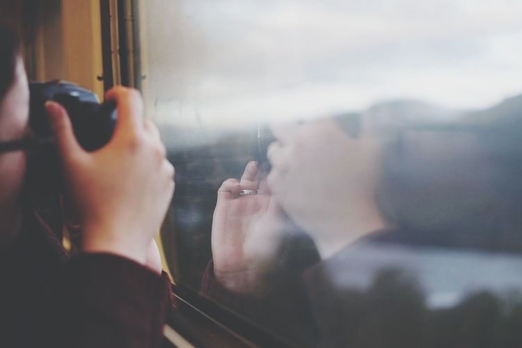 Cropped image of man photographing through camera while sitting in train