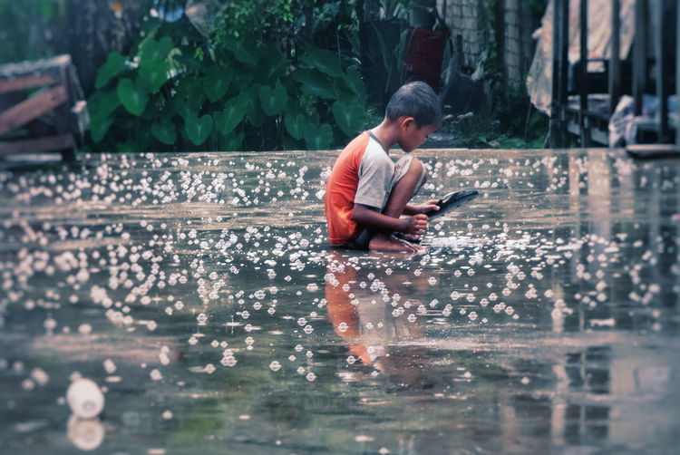 Side view of boy using mobile phone in water