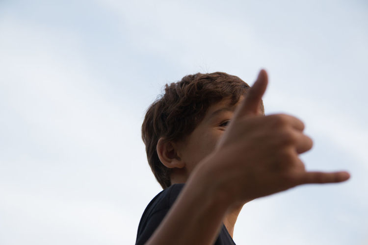 Low angle portrait of child hand against clear sky