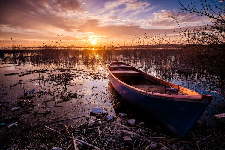 Boat on the lake under sunset. Water Mode Of Transportation Nautical Vessel Sunset Transportation Sky Moored Cloud - Sky Tranquility Tranquil Scene Scenics - Nature Reflection Nature No People Lake Non-urban Scene Abandoned Beauty In Nature Orange Color Sun Outdoors Rowboat