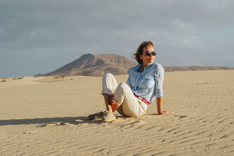 Stylish woman dressed in light clothes standing on blue stairs Desert Dunes Sand Landscape Arid Dry Climate Wild Hot Sandy Corralejo Natural Nature Park Fuerteventura Canary Islands Sitting Woman Female Girl person Young Free Freedom Rest Waiting Mountain Background Model Posing Traveler Caucasian Sunset Evening Golden Alone Single Lost Wanderer Wandering