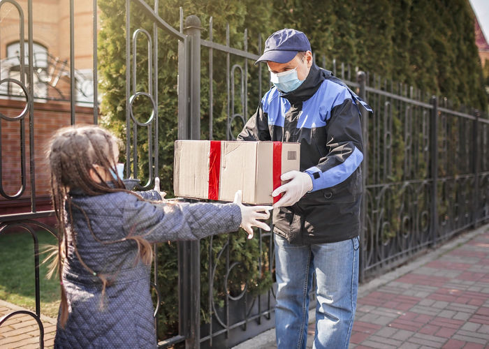 Girl receiving parcel from delivery person outdoors