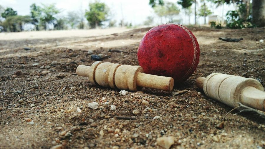 After a hard day's work he's taking some rest. Abandoned Roadside Surface Level Dirt Day Man Made Object Outdoors Dirty Red Obsolete Focus On Foreground Sandy Diminishing Perspective Weathered Cricket Ball Cricket Field