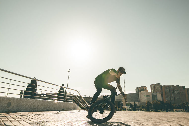 Man riding bicycle in city against clear sky