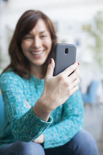 Smiling woman video calling over mobile phone