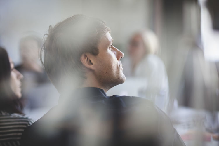 Rear view of businessman listening while sitting in board room during meeting