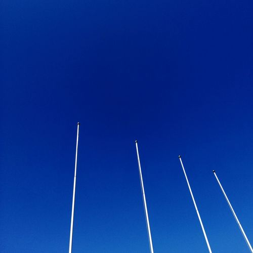 Low angle view of vapor trails against clear blue sky