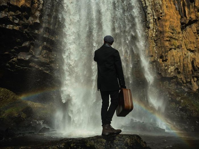 Rear View Of Man Standing On Rock While Holding Briefcase Against Waterfall
