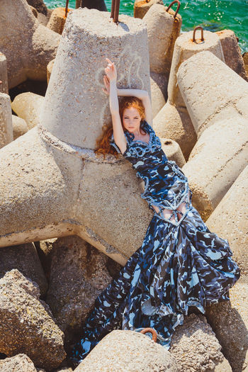 Full length portrait of young woman lying on rock by sea