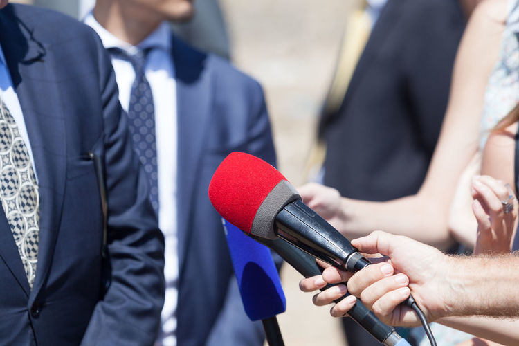 Midsection Of Reporters With Microphones Interviewing Businessmen