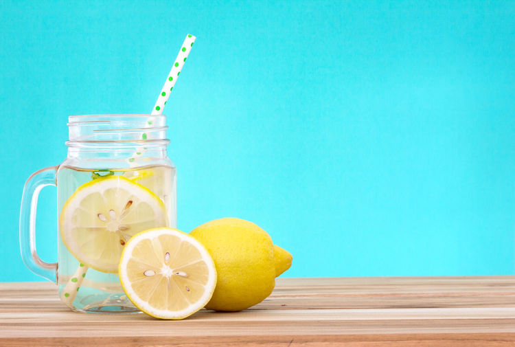 Citrus lemonade water with lemon sliced , healthy and detox water drink in summer on wooden table with blue lighten background Antioxidant Blue Background Citrus Fruit Container Drink Drinking Straw Food Food And Drink Freshness Fruit Glass Healthy Eating Indoors  Jar Lemon No People Refreshment SLICE Sour Taste Still Life Straw Table Vitamin C Wellbeing Wood - Material