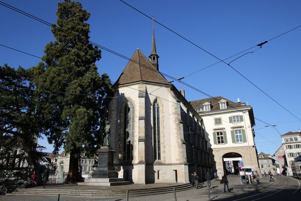 Wasserkirche - Limmatquai, Zurich. The Zurich Wasserkirche (Water Church) is located at Limmatquai 31, on the corner of Munsterbrucke. Trams 4 and 15 stop right outside (Helmhaus tram stop). In front of the Wasserkirche church stands a statue of Ulrich (Huldrych) Zwingli (1 Jan 1484 - 11 Oct 1531). The Swiss Reformer is described as an Humanist, Bible translator, and Head of the Zurich Church. http://pics.travelnotes.org/ Church Kirche Little Big City Michel Guntern Street View Tourist Attraction  Tram Travel Photography Zürich Architecture Blue Sky Building Exterior Clear Sky Daily Life Day Outdoors Place Of Worship Religion Street Photography Swiss Tourism Switzerland Tourism Tram Lines Travel Pics Wasserkirche
