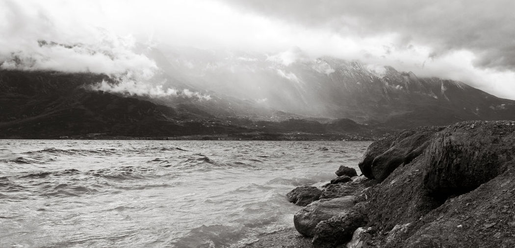 Beach on Limone sul Garda on a stormy day in spring Cool Dramatic Sky Gardasee Lake Garda Limone Limone Sul Garda Nature Panorama Rain Storm Travel Weather Black And White Clouds Dramatic Italy Lake Landscape Nature Rocks Sea Sky Tranquility Water Wind