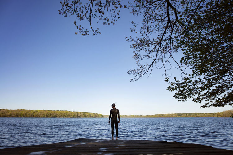 Man standing by lake against clear sky