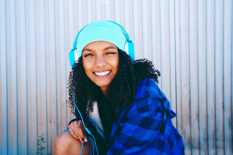 Portrait Of Smiling Woman Listening Music While Winking Against Wall