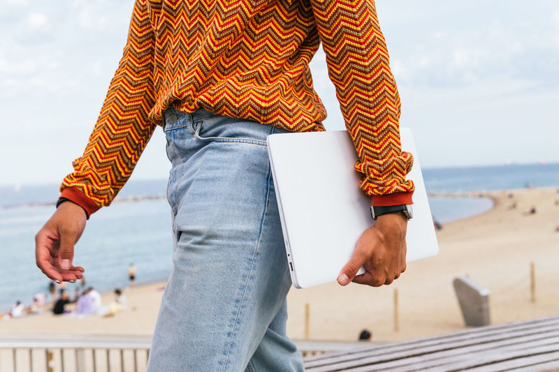 Midsection of man standing at beach against sky