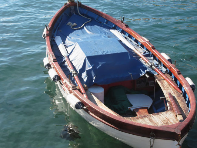 Wooden fishing boat anchored in a village port of Golfo Dei Poeti, Province of La Spezia, Italy Afloat Anchored Blue Boatman Bow Bumper Fishboat Fishing Boat Float Floating On Water Golfo Dei Poeti Italy Moored Nautical Vessel Old Boat Paddle Port Rope Rowing Sea Stern Tiny Transport Water Wooden