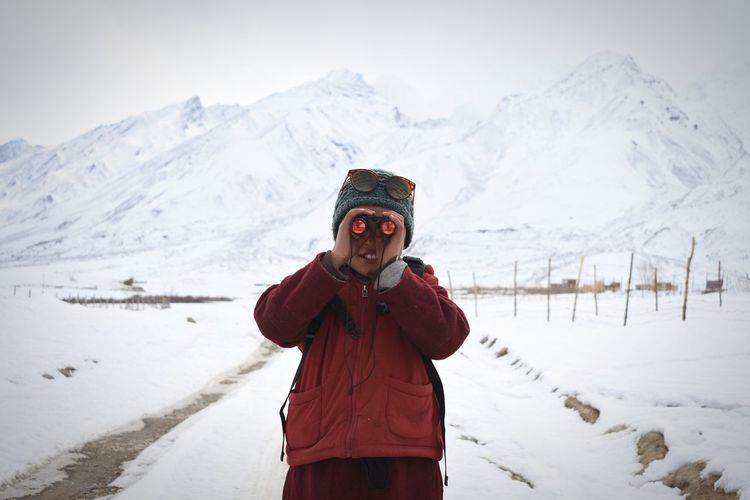 Boy Looking Through Binoculars Against Snowcapped Mountains